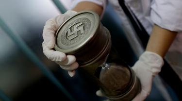 Anggota polisi federal memegang jam pasir dengan tanda Nazi di markas Interpol di Buenos Aires, Argentina, (16/6).  Polisi menemukan 75 koleksi artefak Nazi di ruangan tersembunyi di sebuah rumah kawasan Buenos Aries. (AP Photo/Natacha Pisarenko)