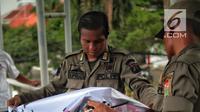 Petugas Satpol PP menertibkan alat peraga kampanye (APK) di jembatan penyeberangan orang (JPO) kawasan Gambir, Jakarta, Sabtu  (22/12). Penertiban itu dilakukan karena melanggar aturan pemasangan dari komisi pemilihan umum. (Liputan6.com/Faizal Fanani)