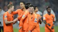 Para pemain Belanda merayakan keberhasilan lolos ke Piala Eropa 2020 usai melawan Irlandia Utara di Windsor Park, Belfast, Sabtu (16/11). Kedua negara bermain imbang 0-0. (AFP/Mark Marlow)
