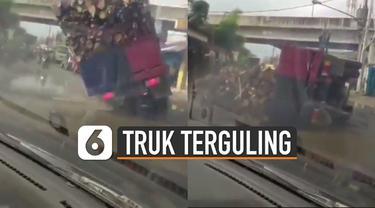 Video sebuah truk bermuatan kayu terguling akibat jalanan berlubang viral di media sosial.