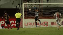 Kiper Persija Jakarta, Andritany Ardhiyasa (tengah) berusaha menangkap bola hasil tendangan pemain PSM Makassar dalam laga leg pertama semifinal Piala Menpora 2021 di Stadion Maguwoharjo, Sleman, Kamis (15/4/2021). (Bola.com/Ikhwan Yanuar)