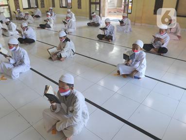 Sejumlah santri berusia belasan tahun membaca Al quran atau tadarus bersama-sama dengan menerapkan jaga jarak di Masjid Daarul Qu'ran Pesantren Al Kautsar, Cibinong, Bogor, Kamis (7/5/2020). Kegiatan Khatam Al quran tersebut dilakukan rutin di setiap bulan Ramadan. (merdeka.com/Arie Basuki)