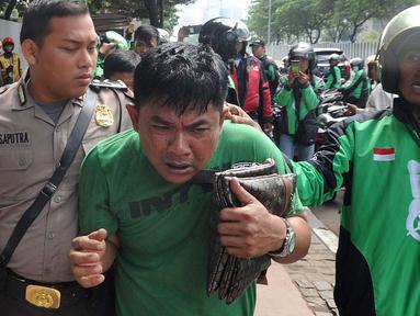 Petugas kepolisian mengamankan terduga copet menuju Mapolda Metro Jaya di Jalan Jenderal Sudirman, Jakarta (2/4). Pelaku tertangkap tangan oleh korbannya saat mencopet handphone di jembatan penyeberangan orang (JPO). (Merdeka.com/Arie Basuki)