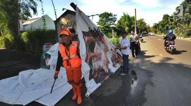 Petugas Bawaslu melakukan pencopotan alat peraga kampanye (APK) Pemilu 2019 di kawasan Lebak Bulus, Jakarta Selatan, Minggu (14/4). Pencoptan yang melibatkan tenaga PPSU ini sebagai tindak lanjut masa tenang Pemilu 2019 hingga hari pencoblosan 17 April mendatang. (merdeka.com/Arie Basuki)