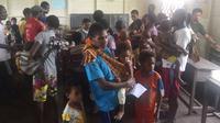 Sejumlah warga dan anak mereka antre mendapatkan pengobatan dan vaksin campak di Kabupaten Asmat, Papua, Jumat (19/1). Satgas Kesehatan TNI menyalurkan bantuan berupa vaksin ke kampung-kampung terpencil di Kabupaten Asmat. (LIputan6.com/Pool/Puspen TNI)