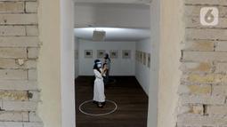 Pengunjung berjaga jarak fisik saat melihat pameran karya pelukis Hanafi berjudul 60 tahun dalam studio di Galerikertas, Depok, Jawa Barat, Selasa (7/7/2020).  Pameran tersebut menerapkan protokol kesehatan guna mencegah penyebaran COVID-19. (merdeka.com/Arie Basuki)