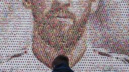 Seorang bocah memperhatikan mural Lionel Messi di Casa Rosada Museum, Buenos Aires, Argentina, Rabu (20/6). Mural terbuat dari dua ribu stiker figur pemain Argentina dalam Piala Dunia sepanjang masa. (Eitan ABRAMOVICH/AFP)