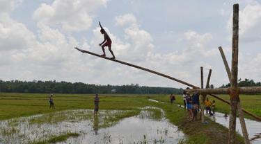 Pemuda Sri Lanka berusaha memanjat batang pohon selama perayaan Tahun Baru Sinhala dan Tamil di Bandaragama, Kolombo (21/4). Sejumlah perlombaan diadakan saat tahun baru umat Hindu, Sinhala dan Tamil yang jatuh 14 April. (AFP Photo/Lakruwan Wannirachchi)