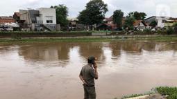 Petugas berdiri di bantaran Sungai Ciliwung di kawasan Rawajati,  Jakarta, Selasa (25/2/2020). Adanya seorang warga yang hanyut saat berenang di tengah luapan Sungai Ciliwung tersebut mengundang perhatian warga serta petugas yang mencari keberadannya. (Liputan6.com/Immanuel Antonius)