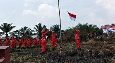 Personel Manggala Agni mengibarkan bendera dalam upacara kemerdekaan di lokasi kebakaran lahan.