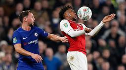 Pemain Arsenal, Alex Iwobi mengendalikan bola di depan pemain Chelsea, Danny Drinkwater pada laga semifinal pertama Piala Liga Inggris di Stadion Stamford Bridge, Rabu (10/1). Chelsea dan Arsenal bermain imbang tanpa gol. (AP/Kirsty Wigglesworth)