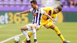 Bek Barcelona, Gerard Pique, berebut bola dengan pemain Real Valladolid, Oscar Plano, pada laga La Liga di Stadion Jose Zorrilla, Sabtu (11/7/2020). Barcelona menang 1-0 atas Real Valladolid. (AP Photo/Manu Fernandez)