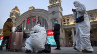 Penumpang yang mengenakan pakaian pelindung berkumpul di luar Stasiun Hankou, Wuhan, Provinsi Hubei, China, Rabu (8/4/2020). Setelah 11 minggu lockdown, layanan kereta di kota yang menjadi titik awal pandemi virus corona COVID-19 ini kembali beroperasi. (AP Photo/Ng Han Guan)