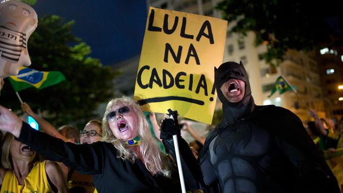 Seorang demonstran mengenakan kostum Batman saat mengikuti aksi protes di Rio de Janeiro, Brasil (3/4). Luiz Inacio Lula da Silva dijatuhi hukuman penjara hampir 10 tahun karena terbukti melakukan korupsi dan menerima suap. (AP / Silvia Izquierdo)