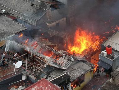 Warga berusaha memadamkan api dengan menyiramkan air saat terjadi kebakaran di kawasan Tanah Tinggi, Johar Baru, Jakarta, Selasa (26/6). Sebanyak 18 unit mobil pemadam kebakaran telah diterjunkan ke lokasi. (Liputan6.com/Arya Manggala)