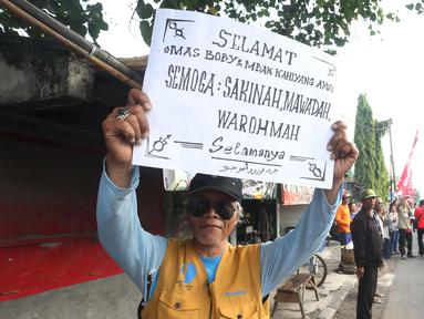 Warga menunjukkan poster bertuliskan selamat untuk pernikahan putri Presiden Jokowi,  Kahiyang Ayu dan Bobby Nasution saat menyaksikan prosesi kirab kereta kencana menuju Gedung Graha Saba di Surakarta, Rabu (8/11). (Liputan6.com/Angga Yuniar)