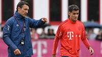 Pemain Bayern Munchen, Philippe Coutinho, mendengarkan instruksi Niko Kovac saat latihan perdananya di Munchen, Selasa (20/8). Bintang Brasil ini didatangkan dari Barcelona. (AFP/Christof Stache)