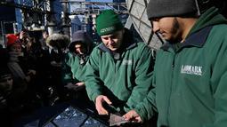 Para pekerja bersiap memasang kristal berbentuk segitiga pada bola kristal di atas One Times Square, New York, Rabu (27/12). Bola yang menjadi icon malam tahun baru di New York itu dirancang khusus oleh seniman-seniman Waterford. (AP/Seth Wenig)
