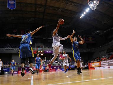 Pemain CLS Knight, Rachmad Febri Utomo melakukan lay up saat dihadang pemain Satya Wacana pada perempat final Playoffs Indonesia  Basket League (IBL) di Britama Arena, Jakarta, Selasa (17/5/2016). (Bola.com/Nicklas Hanoatubun)