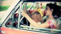 (Ilustrasi) Berkendara sambil memangku anak sangat berbahaya. (Dissolve)