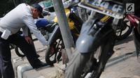 Petugas Dishub DKI menggembosi ban sepeda motor yang nekat parkir liar di trotoar sepanjang Jalan Kramat Raya, Senen, Jakarta, Jumat (22/9). Razia dilakukan untuk mengembalikan fungsi trotoar sebagai jalur pedestrian. (Liputan6.com/Faizal Fanani)