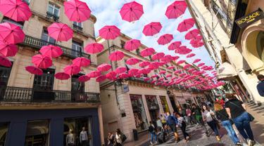 Orang-orang berjalan di bawah ratusan payung pink yang digantung untuk meningkatkan kesadaran deteksi dini kanker payudara di Montpellier, Prancis, Selasa (9/10). Bulan Oktober, ditetapkan sebagai bulan kewaspadaan atas kanker payudara. (AFP/PASCAL GUYOT)