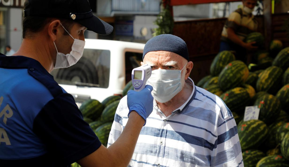 Petugas kota memeriksa suhu tubuh seorang pria di sebuah pasar di Istanbul, Turki (11/8/2020). Otoritas lokal di Istanbul telah meningkatkan upaya untuk mendeteksi infeksi COVID-19 secara cepat saat jumlah kasus baru harian di Turki mengalami peningkatan. (Xinhua/Osman Orsal)