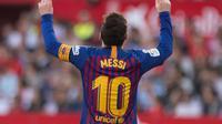 Penyerang Barcelona Lionel Messi menunjuk langit usai mencetak gol ke gawang Sevilla pada laga La Liga di Stadion Ramon Sanchez Pizjuan, Sevilla, Sabtu (23/2). Messi mencetak hattrick. (JORGE GUERRERO/AFP)