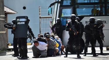 Polisi antiteror membebaskan wisatawan yang disandera dalam simulasi penanggulangan teror di Pelabuhan Benoa, Bali, (8/3). Simulasi penanggulangan teror di kawasan pelabuhan wisata itu atas kerja sama Indonesia-Inggris. (AFP Photo/Sonny Tumbelaka)