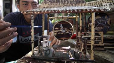 Perajin, Inoe Farhand menyelesaikan pembuatan miniatur jam dari pelepah pisang di Pamulang, Tangsel, Kamis (10/1). Dalam sehari Inoe mampu menyelesaikan dua buah kerajinan tangan seperti miniatur becak, mobil VW dan Kapal phinisi (Merdeka.com/Arie Basuki)