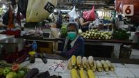 Pedagang mengenakan masker yang dibagikan petugas Polres Jakarta Timur selama sosialisasi di Pasar Palmeriam, Matraman, Selasa (9/2/2021). Kegiatan tersebut sebagai upaya meningkatkan kesadaran akan pentingnya penerapan protokol kesehatan untuk menekan penyebaran Covid-19. (merdeka.com/Imam Buhori)