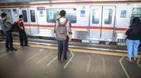 Penumpang berdiri di garis antrean penumpang di Stasiun Juanda, Jakarta, Kamis (10/8). PT KAI Commuter Jabodetabek melakukan uji coba garis antrean penumpang tersebut guna untuk keselamatan bagi para penumpang. (Liputan6.com/Faizal Fanani)