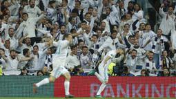 Suporter ikut merayakan gol Karim Benzema saat melawan Bayern Munchen pada leg kedua semifinal Liga Champions di Santiago Bernabeu stadium, Madrid, (1/5/2018). Madrid bermain imbang 2-2. (AP/Paul White)