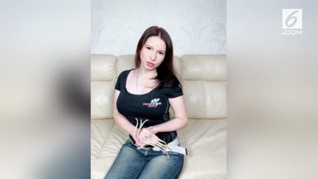 Orang dengan kuku terpanjang di Rusia tunjukkan caranya berpakaian untuk sehari-hari.
