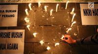 Lilin simbol cinta dinyalakan oleh gabungan suporter klub sepak bola dalam aksi solidaritas terkait tragedi teror bom di Surabaya dan Sidoarjo di Taman Suropati, Jakarta, Senin (14/5). (Liputan6.com/Immanuel Antonius)
