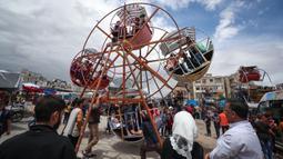 Anak-anak Suriah bermain di taman hiburan sementara ketika merayakan Idul Fitri yang menandai akhir bulan suci Ramadan di kota Idlib, Suriah, Senin (24/5/2020). Anak-anak tersebut menikmati permainan yang mungkin jarang mereka rasakan di tengah peperangan yang masih berkecamuk. (OMAR HAJ KADOUR/AFP)