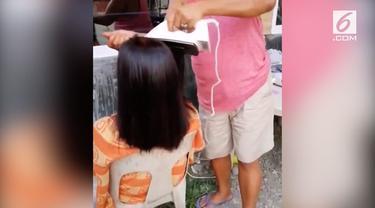 Seorang emak-emak kini tengah menjadi perbincangan hangat. Ia meluruskan rambut kerabatnya menggunakan setrika baju.