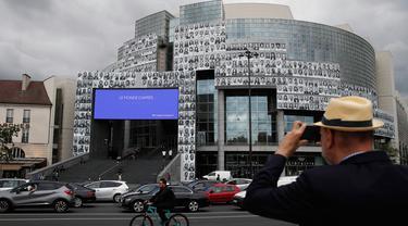Seorang pria mengambil gambar potret para petugas kesehatan yang ditempelkan di bagian depan Bastille Opera di Paris, Prancis, Jumat (10/7/2020). Potret hitam putih itu untuk memberi penghormatan kepada pekerja medis yang berjuang menghadapi Corona Covid-19. (AP Photo/Francois Mori)