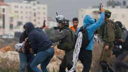 Polisi Israel menangkap seorang demonstran Palestina di kota Ramallah, Tepi Barat, (13/12). Sejumlah Polisi Israel menangkap warga Palestina dengan menyamar sebagai demonstran. (AP Photo / Nasser Shiyoukhi)