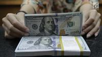 Teller menghitung mata uang dolar di penukaran uang di Jakarta, Jumat (20/4). Nilai tukar rupiah terhadap dolar AS pagi ini melemah ke posisi di Rp 13.820. (Liputan6.com/Angga Yuniar)