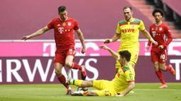 Striker Bayern Munchen, Robert Lewandowski, berusaha melewati pemain FC Koln, Jorge Meré, pada laga Bundesliga di Stadion Allianz, Minggu (27/2/2021). Bayern menang dengan skor 5-1. (AP/Andreas Schaad)