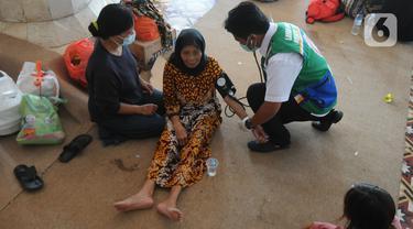 Paramedis memeriksa kesehatan pengungsi korban ledakan kilang minyak di Pendopo Kabupaten Indramayu, Senin (29/03/2021). Sekitar 900 warga saat ini mengungsi dari lima desa terdampak ledakan kilang minyak Balongan.  (merdeka.com/Arie Basuki)
