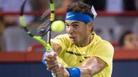 Petenis Spanyol, Rafael Nadal mengembalikan bola ke arah petenis Kanada, Denis Shapovalov pada turnamen Piala Rogers di Montreal, Kamis (10/8). Nadal disingkirkan petenis 18 tahun dengan skor 6-3, 4-6, 6-7. (Paul Chiasson/The Canadian Press via AP)