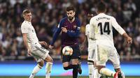 Aksi Gerard Pique melewati Toni Kross pada laga semfinal Copa Del Rey yang berlangsung di stadion Santiago Bernabeu, Madrid, Kamis (28/2). Barcelona menang 3-0 atas Real Madrid. (AFP/Oscar Del Pozo)