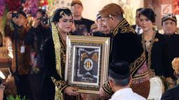 Bobby Nasution saat menyerahkan mas kawin ke Kahiyang Ayu setelah melangsungkan akad nikah di  Graha Saba Buana, Solo, Rabu (8/11). (Liputan6.com/Pool/Jimboengphoto)