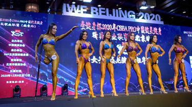Atlet Binaraga asal China, Gui Yuna (kiri) melambaikan tangan dalam ajang International Weightlifting Federation (IWF) Beijing 2020 di Beijing, China, Jumat (11/12/2020). (AFP/NOEL CELIS)