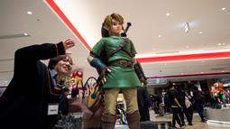 Seorang lelaki berpose di sebelah Link, salah satu karakter Legend of Zelda, permainan legendaris dari Nintendo selama pratinjau pers di toko baru Nintendo di Tokyo, 19 November 2019. Nintendo akan meresmikan toko pertamanya di ibu kota Jepang tersebut pada pekan ini. (Behrouz MEHRI/AFP)