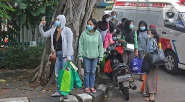 Sejumlah pasien Covid-19 Tanpa Gejala bersiap menaiki bus sekolah di Puskesmas Kecamatan Cilandak, Jakarta, Kamis (4/2/2021). Data Satgas Covid-19 per Kamis (4/2) mencatat kasus positif di Indonesia bertambah 11.434 orang. (Liputan6.com/Herman Zakharia)