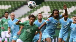 Pemain Werder Bremen, Yuya Osako, berebut bola dengan pemain Wolfsburg, Kevin Mbabu, pada laga Bundesliga di Weserstadion Minggu (7/6/2020). Werder Bremen takluk 0-1 dari Wolfsburg. (AFP/Patrik Stollarz)