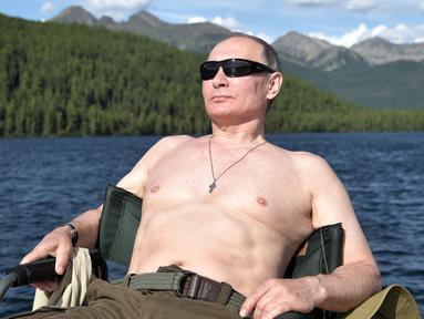 Foto yang dirilis oleh layanan pers Kremlin pada hari Sabtu, 5 Agustus 2017, Presiden Rusia Vladimir Putin beristirahat setelah memancing selama liburan mini di kawasan Siberia Tyva. (Alexei Nikolsky / Sputnik, Foto Kolam Kremlin via AP)